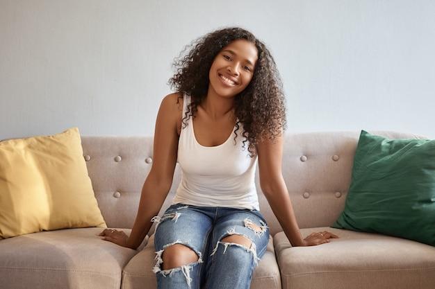 사람과 생활 양식. 파란색 찢어진 청바지와 흰색 탱크 탑에서 아름 다운 젊은 어두운 피부 여자 집에서 휴식, 쿠션이있는 편안한 회색 소파에 앉아 광범위하게 미소