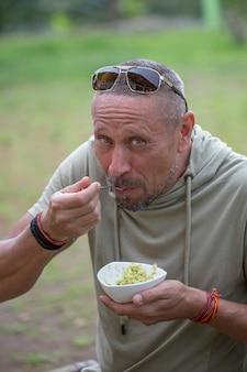 Люди и концепция образа жизни. счастливый мужчина средних лет ест авокадо гуакамоле на природе, крупным планом портрет Premium Фотографии