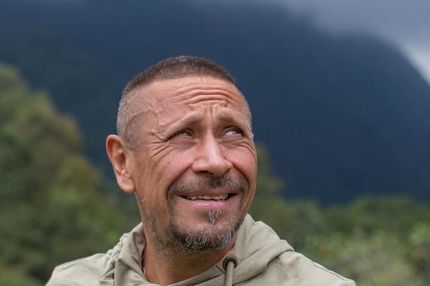 Люди и концепция образа жизни. счастливый небритый мужчина средних лет, открытый на фоне зеленой природы. портрет взрослого человека крупным планом