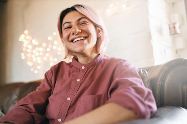 人とライフスタイルのコンセプト。のんきな幸せな若いヨーロッパの女性の屋内イメージは、鼻ピアスがリビングルームでリラックスし、ソファに快適に座って、家にいるのが心地よく、笑っています。