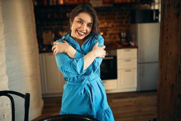 人とライフスタイルのコンセプト。彼女の胸に腕を組んで、幸せそうな表情を持って、彼女の胸に腕を組んでキッチンのインテリアの背景に立っている魅力的な笑顔で魅力的なかわいい若い女性の屋内ショット