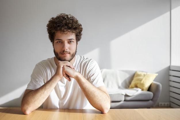 人とライフスタイルのコンセプト。ボリュームのある髪型と厚いひげの笑顔、自宅で余暇を過ごし、木製のテーブルに隔離されて座っているポジティブなハンサムな若い白人男性の屋内ショット