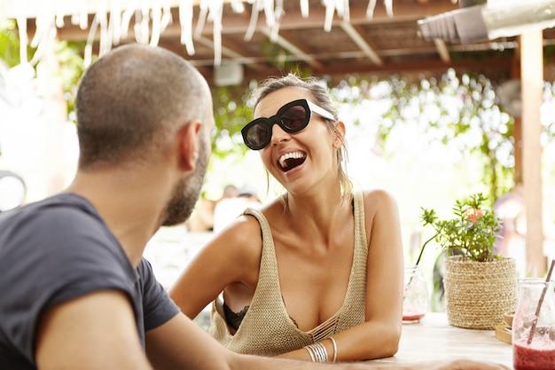 人とライフスタイルのコンセプトです。スタイリッシュな色合いの女性の屋外撮影、晴れた日にカフェでリラックスした日中にひげを生やした男のジョークを笑って。