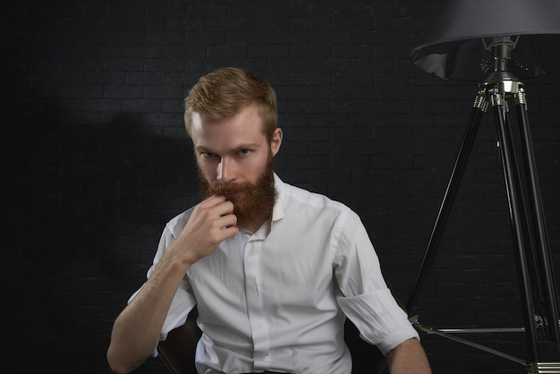 人とライフスタイルのコンセプト。暗い部屋に座っている白いシャツを着ている暗い深刻な若い赤い髪の男性の写真