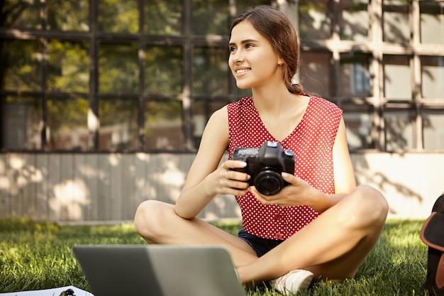 人とライフスタイルのコンセプト。ポータブルコンピューターの前の草の上に座っているデジタル一眼レフカメラを保持し、夏の写真撮影の写真をレタッチするスタイリッシュな服を着たプロの女性写真家の写真