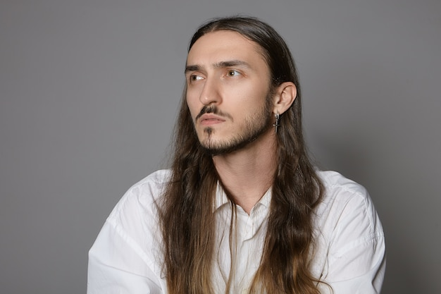 人とライフスタイルのコンセプト。白いシャツを着て屋内でポーズをとって、物思いにふける集中した表情をして、働いているか、決断を下している、長い髪とあごひげを持つトレンディな若い創造的な男性の写真