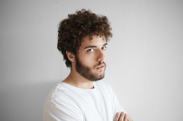 人とライフスタイルのコンセプト。顔の表情を傷つけ、屋内でポーズをとり、失望した表情をしたボリュームのある髪型の真面目な若いひげを生やした男