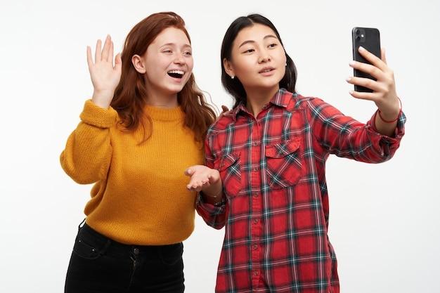사람과 라이프 스타일 개념. 두 명의 귀여운 소녀. 노란색 스웨터와 체크 무늬 셔츠를 입고. 소녀는 화상 통화로 친구를 부모에게 소개합니다. 셀카 만들기. 흰 벽 위에 절연 스탠드