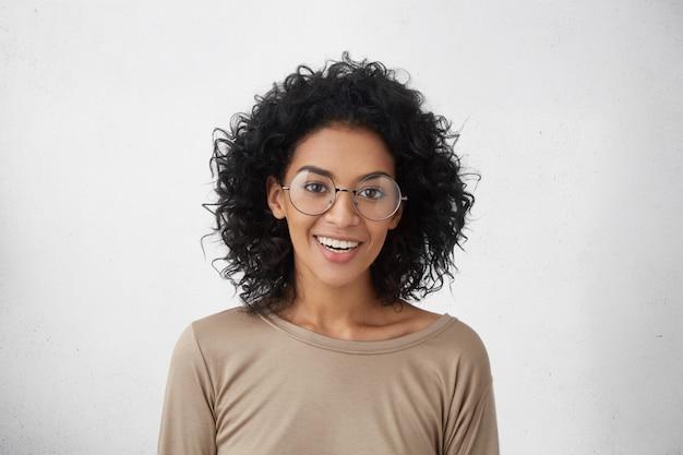 人とライフスタイル。感情と感情。大学での初日について興奮しているカジュアルな服装とスタイリッシュな丸い眼鏡の幸せな笑顔でかわいい肯定的な浅黒い肌の学生女性