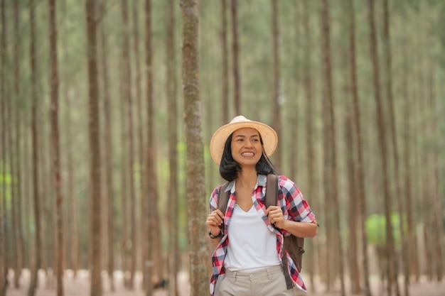 사람과 라이프 스타일 모험, 여행, 관광, 하이킹 및 사람들 개념-배낭, 숲에서 모자와 함께 걷는 미소의 숲에서 산책하는 여행자 여성.