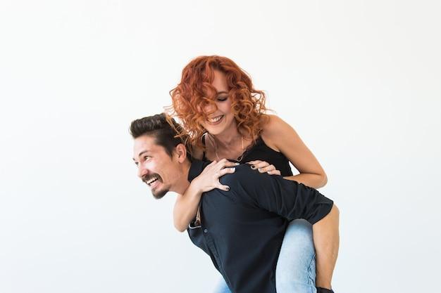 Люди и концепция любви - красивая красивая женщина сидит за спиной мужчины и обнимает его.