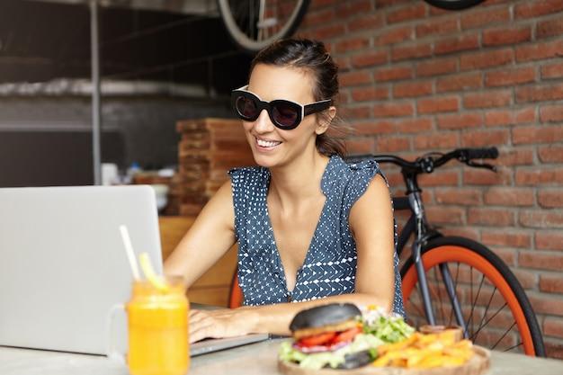 人と現代のテクノロジー。テーブルの上の食物と一緒に開いているラップトップの前に座って無料のwi-fiを楽しんでいるファッショナブルなサングラスのきれいな女性。ノートブックコンピューターを使用して遠くの仕事に女性フリーランサー
