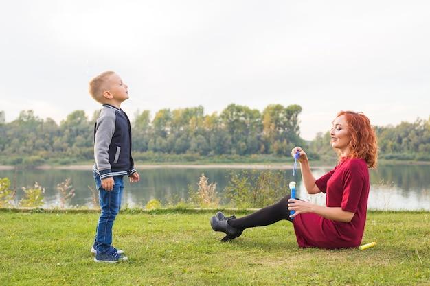 사람과 자연 개념-어머니, 아버지와 다채로운 비누 거품을 가지고 노는 자녀.
