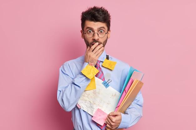 人と職業の概念。丸い眼鏡をかけたショックを受けた男性マネージャーが口を覆い、カメラに驚いた視線がビジネス会議の準備をするドキュメントを保持します