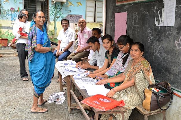 Люди и сотрудники избирательного участка ищут имя избирателя в списке и завершают процесс голосования во время выборов.