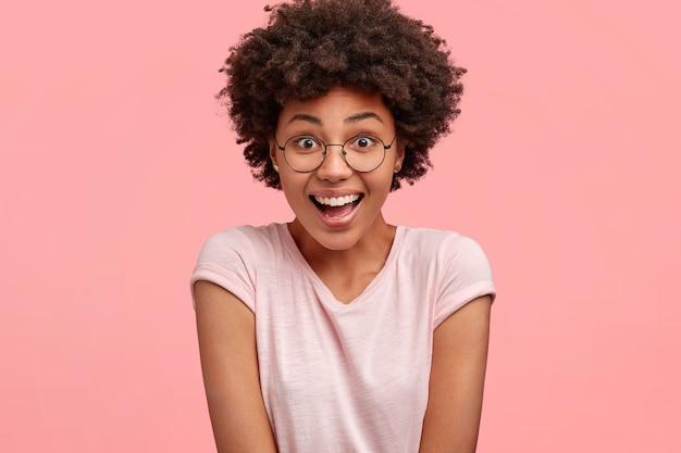人と反応の概念。幸せな大喜びの若いアフリカ系アメリカ人女性は前向きなニュースに反応し、広い笑顔と驚きの表情を持ち、カジュアルなtシャツを着て、ピンクの壁にポーズをとる