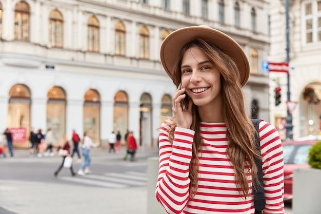 人とレクリエーションの概念。素敵な若い白人女性が現代の携帯電話で友人と通信します