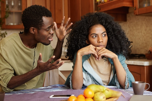 Концепция людей и отношений. афроамериканец пара спорит на кухне: мужчина в очках жесты в гневе и отчаянии, кричать на свою прекрасную несчастную девушку, которая полностью игнорирует его