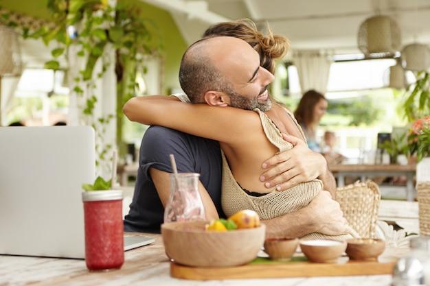 사람과 관계. 카페에서 점심을 먹으면서 포옹, 큰 싸움 후 그것을 만드는 행복 한 커플.