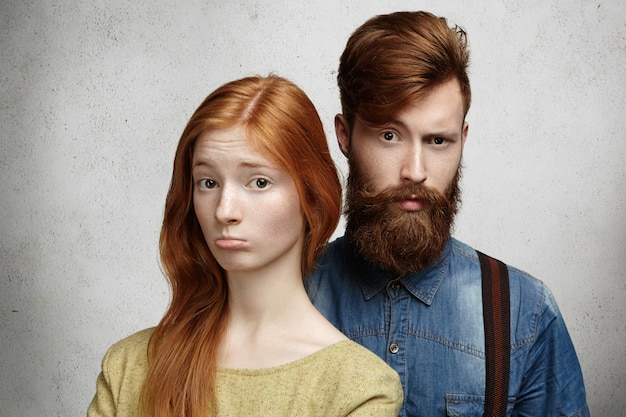 Люди и отношения. молодая кавказская пара с недовольным взглядом ссорится.