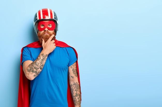 人と超大国のコンセプト。赤い太いひげを持つ真面目な男は、ヘルメットと赤いスーパーヒーローのマントを着ています