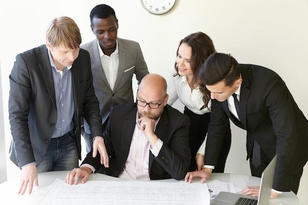 사람과 팀워크 개념. 브레인 스토밍 세션 동안 함께 새 건물의 계획을 작업하는 엔지니어 그룹.