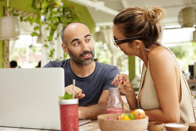 Концепция людей и технологий. красивая пара приятно разговаривает, сидя за столиком в кафе с ноутбуком и смузи на летних каникулах.