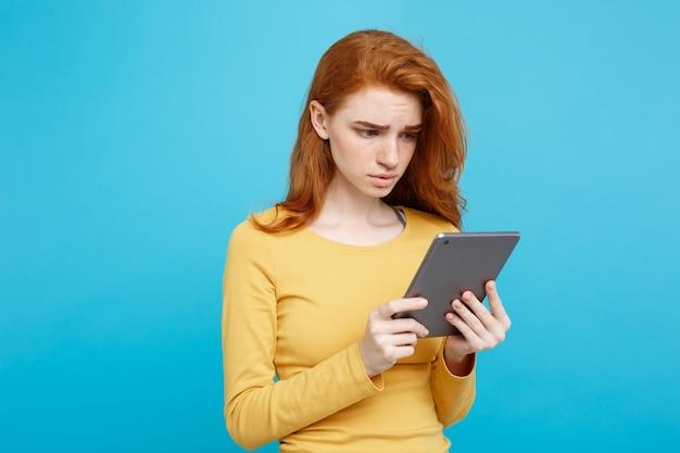人とテクノロジーの概念 - クローズアップ肖像画若い美しい魅力的な柔らかいジンジャー赤毛の女の子衝撃と悲しい何かをワインディングでデジタルテーブル。青いパステルの背景。スペースをコピーします。