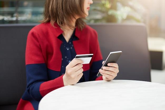 人と技術の概念。クレジットカードを保持しているショッピングモールに座っている赤いカーディガンを着た若い女性の肖像画をトリミング