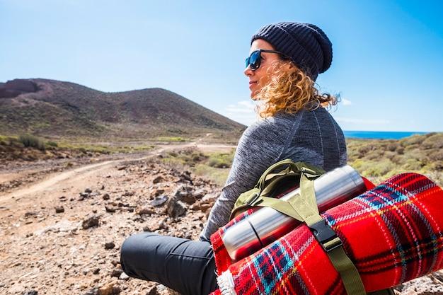 사람과 트레킹 배낭 여행 모험 활동 금발의 여인이 앉아서 하이킹 레저 혼자 라이프 스타일을 즐기는 바다와 계곡이있는 아름다운 경치 좋은 풍경을보고 휴식을 취하십시오.