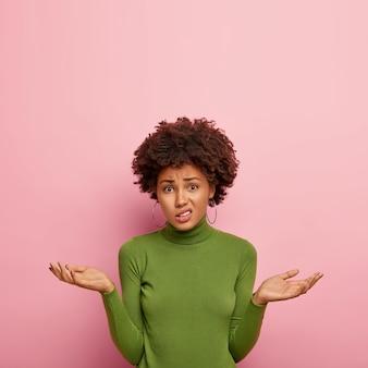 人と不確実性の概念。不機嫌な躊躇している女性モデルは、疑いを持って手のひらを広げ、紛らわしく見え、緑のセーターを着て、ピンクの壁にポーズをとり、スペースを上向きにコピーします