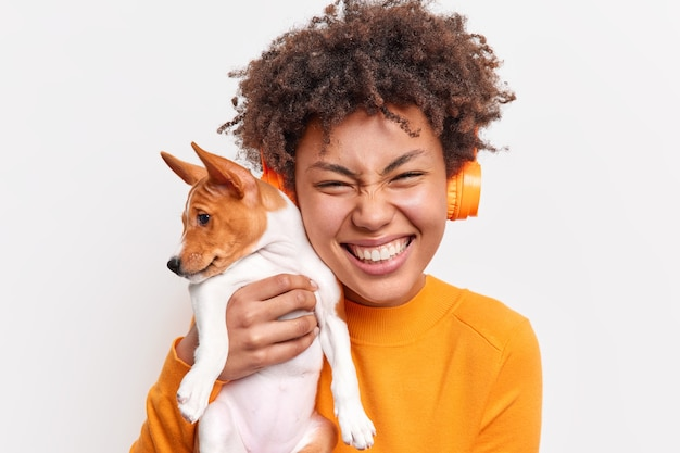 People animals friendship concept. overjoyed curly haired woman smiles tenderly holds small pedigree puppy closely to face listens music via wireless headphones isolated over white wall