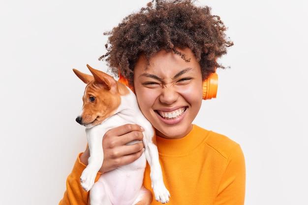Концепция дружбы люди животные. обрадованная кудрявая женщина улыбается, нежно держит маленького породистого щенка вплотную к лицу, слушает музыку через беспроводные наушники, изолированные на белой стене