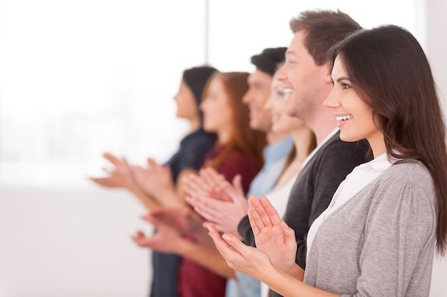 Люди аплодируют. группа веселых молодых людей, стоящих в ряд и аплодирующих кому-то, вид сбоку
