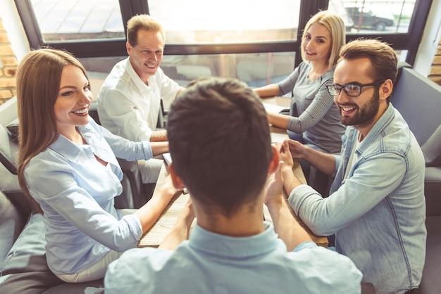Люди обсуждают дела и улыбаются во время работы.
