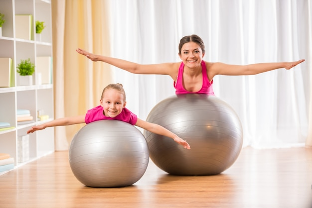 People are doing physical exercises on fitness ball at home.