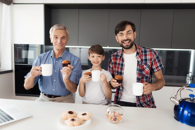 People are drinking tea in kitchen and posing with muffins.