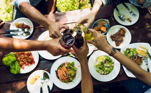 Люди едят в отпуск. они едят вне дома и чокаются пивной.