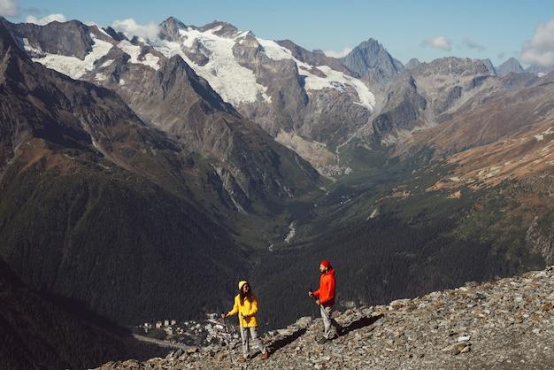 사람들은 산에서 노르딕 워킹에 종사하고 있습니다. 활동적인 커플이 하이킹에 종사하고 있습니다. 젊은 부부가 추적에 종사하고 있습니다. 트레킹과 노르딕 워킹. 등산. 돔베이. 복사 공간