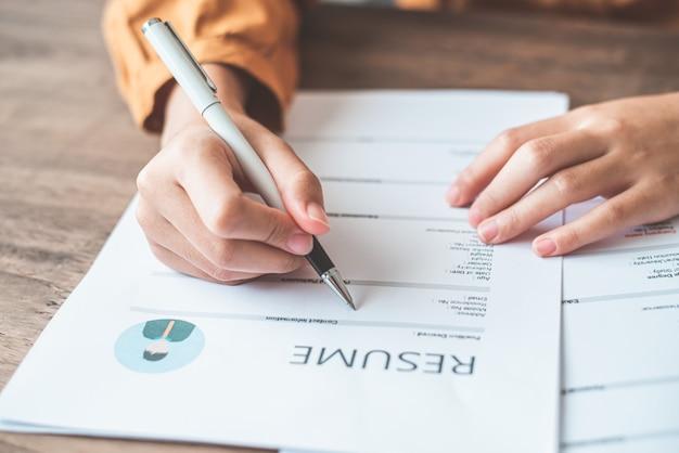 人々は会社での仕事に応募するために求人応募フォームに履歴書を記入しています。