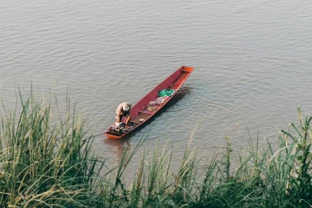人々は水中で小さな漁船で釣りをしています。