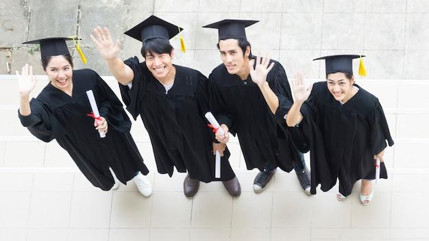 人々は卒業ガウンで幸せであり、ラインでキャップスタンド