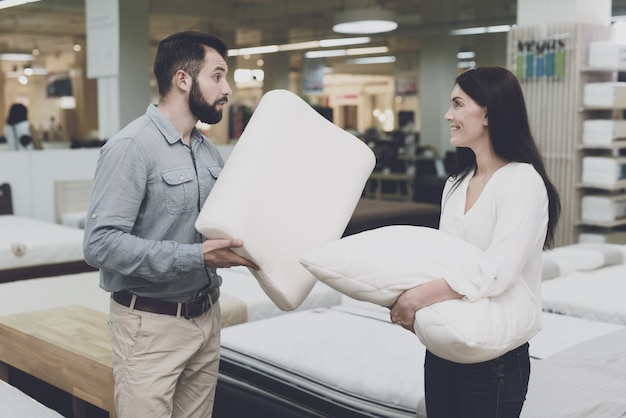 People are holding a pillow in his hands and inspects it.