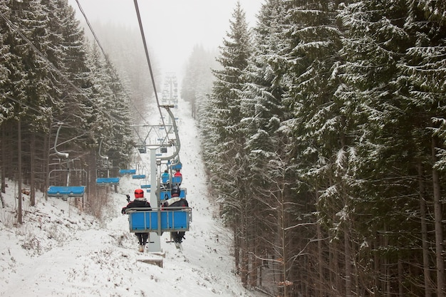 People are lifting on ski-lift in the mountains through the snow-covered forest.