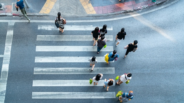 People are moving across the pedestrian crosswalk in the city road (on top view).