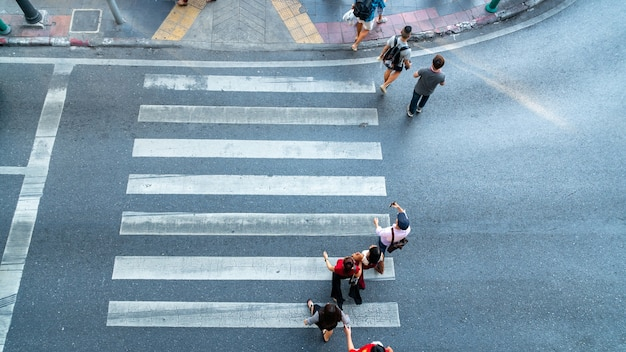 People are moving across the pedestrian crosswalk in the city road