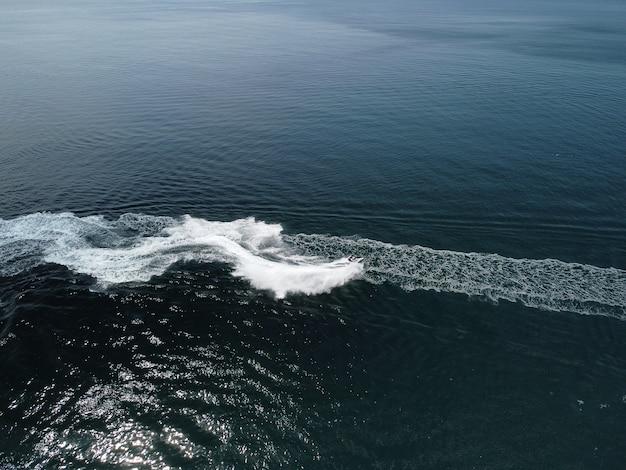사람들이 바다에서 제트 스키를 하고 있으며 수상 공중 꼭대기에 추상적인 흰색 발자국을 남기고 있다