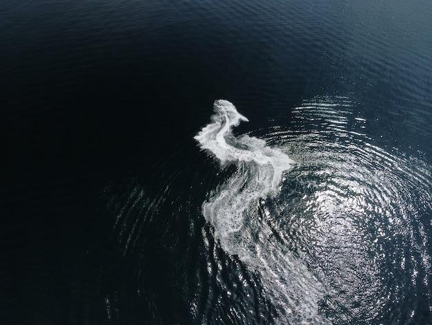 人々は海でジェットスキーをしていて、水上空中の頂上に抽象的な白い足跡を残しています