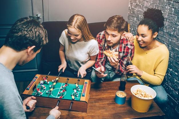 Люди играют в настольную игру в футбол на столе