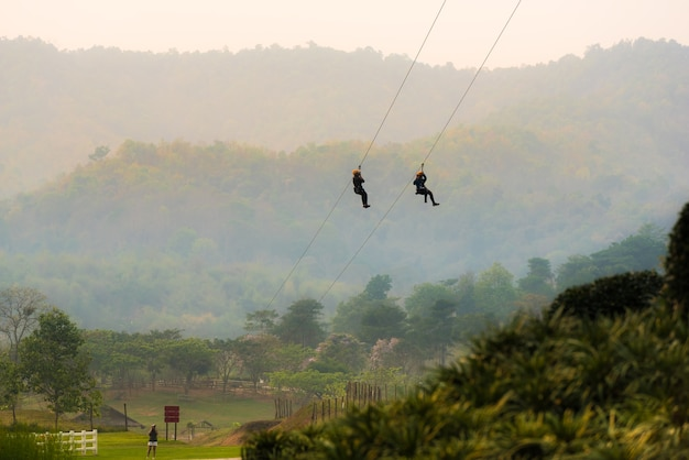 People are playing zipline which is a challenging activity